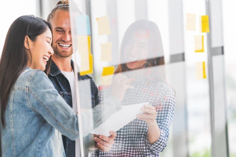 不同种族的不同的队会议在透明玻璃,柱子贴纸,坦率的微笑一起写项目目标计划 免版税库存图片