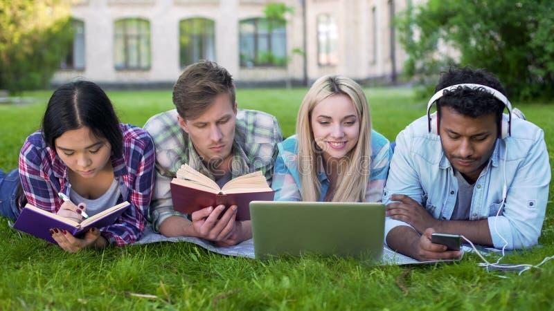 不同种族的做在草的男人和妇女家庭作业在校园里,高等教育 库存照片