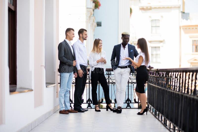 不同种族的商人有咖啡休息在办公楼阳台  免版税库存照片