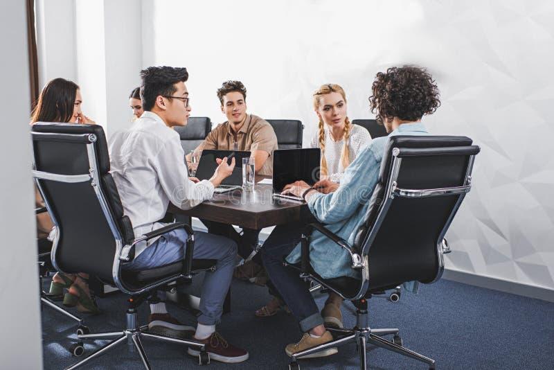 不同种族的商人有讨论在与膝上型计算机的桌上在现代 免版税库存图片