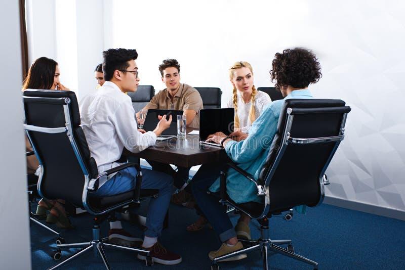 不同种族的商人有讨论在与膝上型计算机的桌上在现代 图库摄影