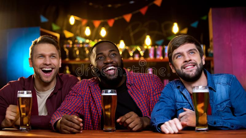不同种族的在大屏幕上的朋友微笑的观看的喜剧在啤酒客栈,乐趣 免版税库存图片