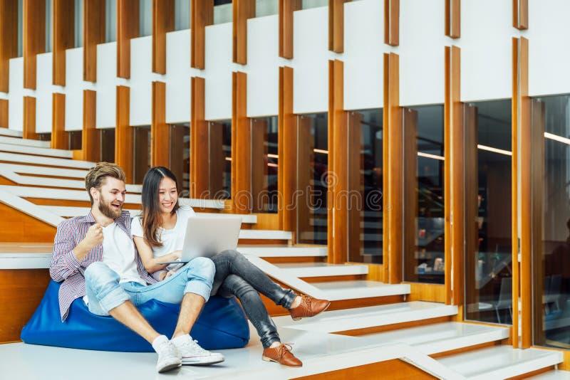 不同种族的大学生夫妇与在台阶的膝上型计算机一起庆祝在大学或现代办公室里 免版税库存图片