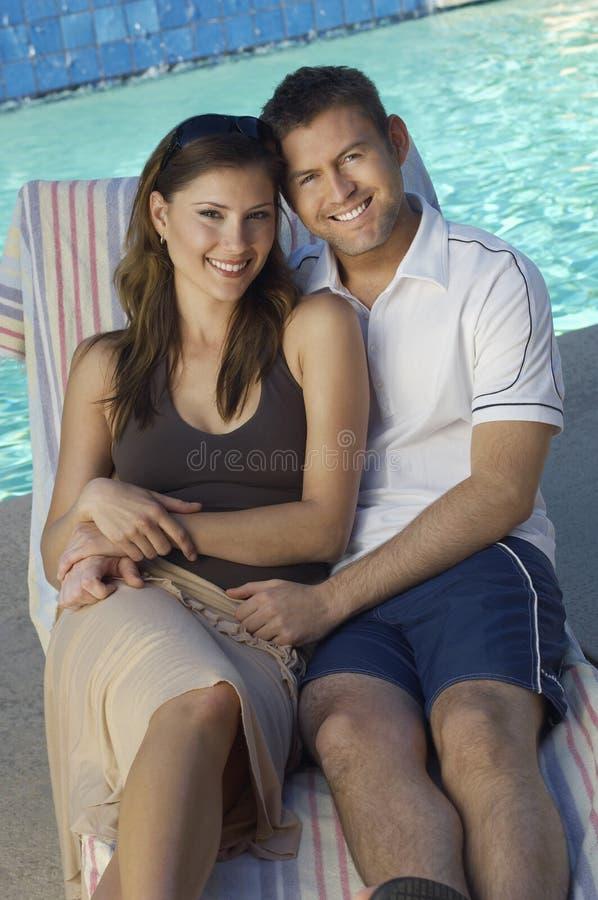 不同种族的夫妇一起坐轻便折叠躺椅 免版税库存照片