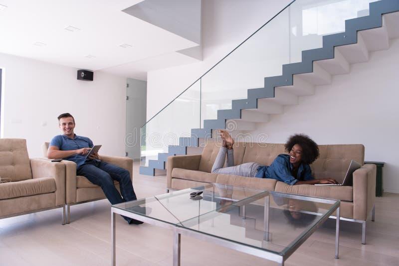 年轻不同种族的夫妇在客厅放松 库存图片