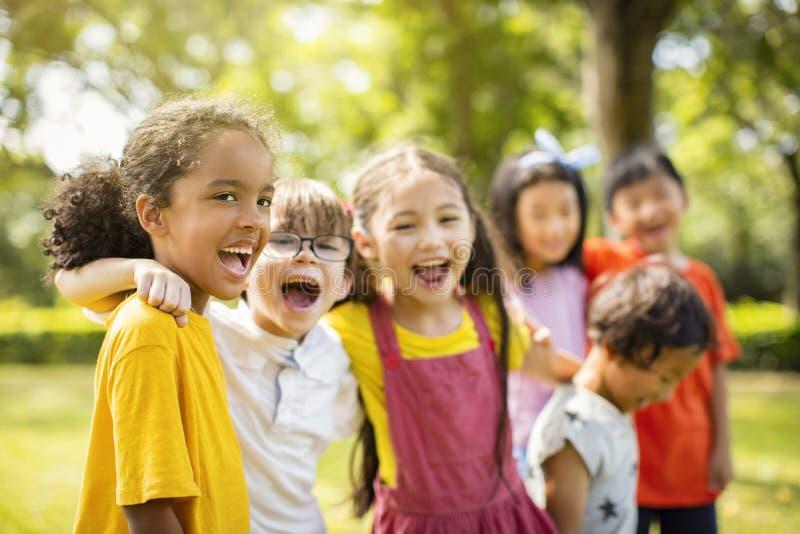 不同种族的小组拥抱的小学生笑和 库存图片