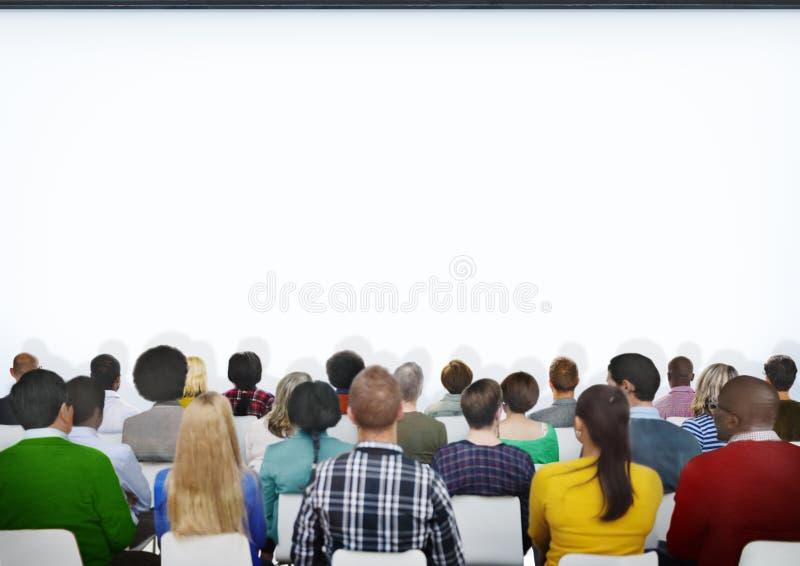 不同种族的小组与拷贝空间的观众 图库摄影