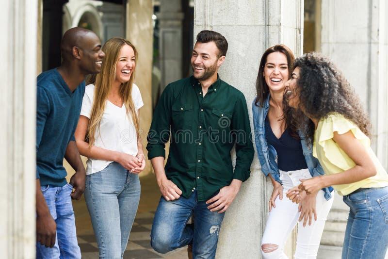 不同种族的小组朋友获得乐趣一起在都市backg 免版税库存图片