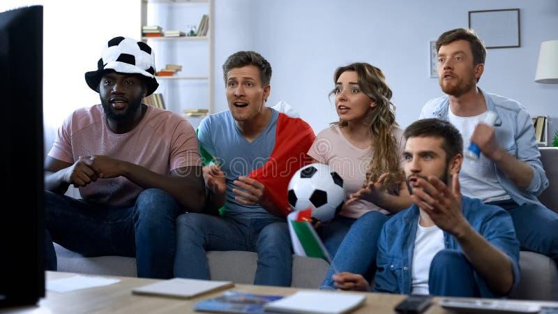 不同种族的意大利爱好者坐沙发和观看的比赛,流动代课教师组 库存照片