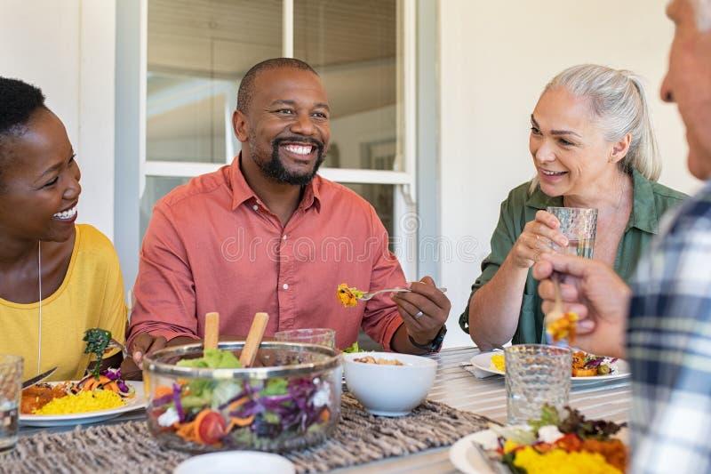 不同种族的成熟吃午餐的男人和妇女 免版税库存照片