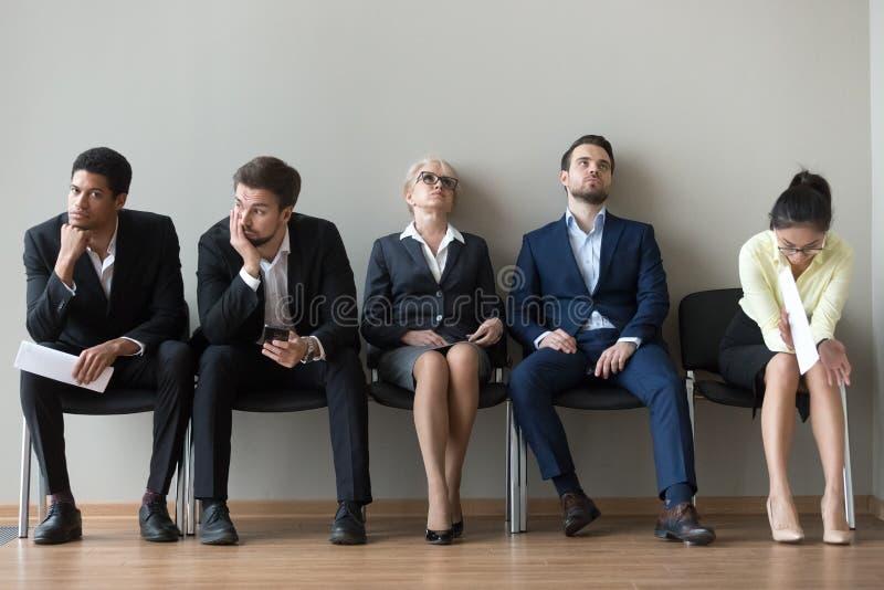 不同种族的求职者疲倦了于等在队列intervi 免版税库存照片