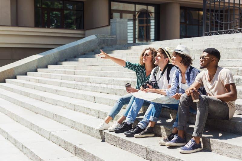 不同种族的游人坐有地图的台阶 免版税库存照片