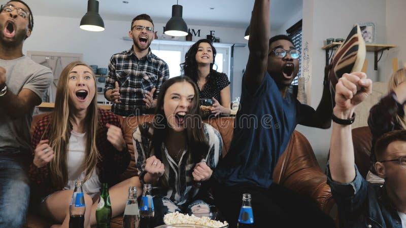 不同种族的爱好者变疯狂庆祝在电视的目标 热情的橄榄球支持者尖叫与胳膊被提出的4K慢动作 免版税库存照片