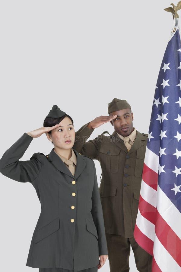 不同种族的美军任命在灰色背景的向致敬的美国国旗军官 库存照片