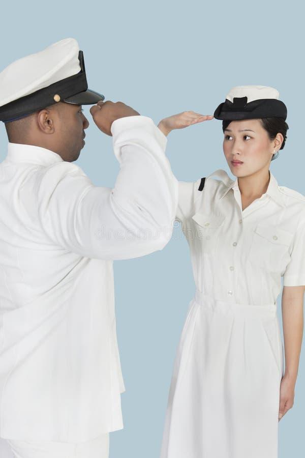 不同种族的美国海军任命向致敬军官在浅兰的背景 免版税库存照片