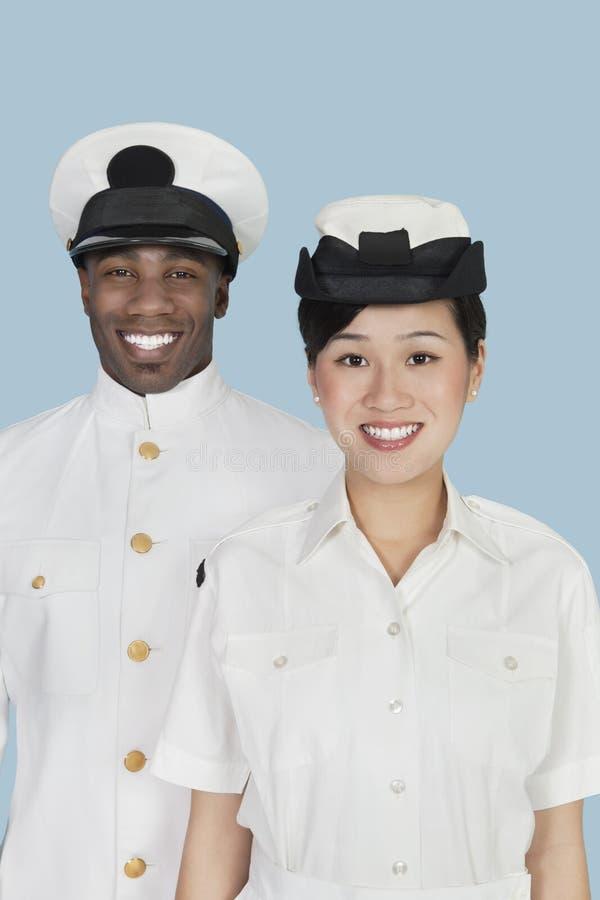 不同种族的美国海军画象任命微笑在浅兰的背景军官 库存照片