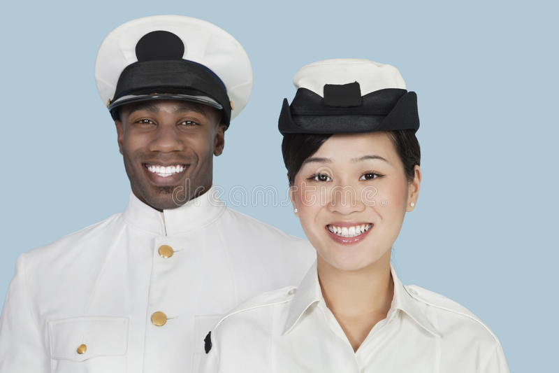 不同种族的美国海军画象任命微笑在浅兰的背景军官 免版税库存图片