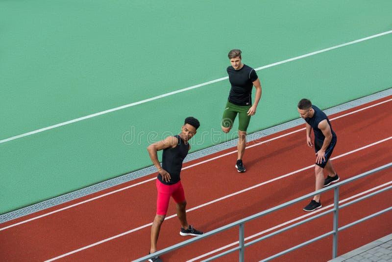 年轻不同种族的运动员小组做舒展锻炼 免版税库存照片
