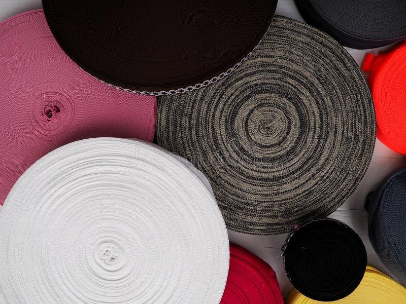 不同颜色丝带在卷的,纺织工业的,衣物制造业许多多彩多姿的卷 免版税库存图片