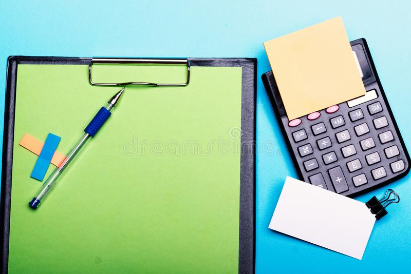 不同颜色书签在笔附近的在绿色夹子文件夹 库存照片