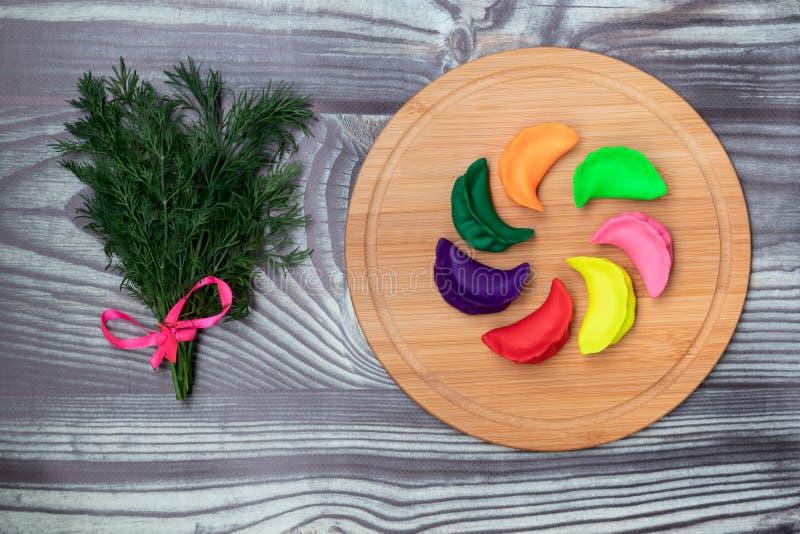 不同颜色和新调味料饺子在一个竹委员会根据传统俄国食谱 免版税库存图片
