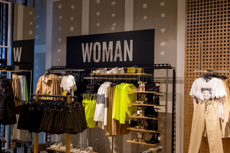 不同颜色妇女的衣物在挂衣架和鞋子的在商店,与白色字法的一块牌里面的架子 库存照片