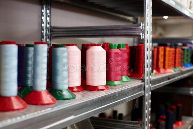 不同,五颜六色的缝合针线,皮革零件的,安排在架子,用于鞋子的生产,提包 免版税图库摄影