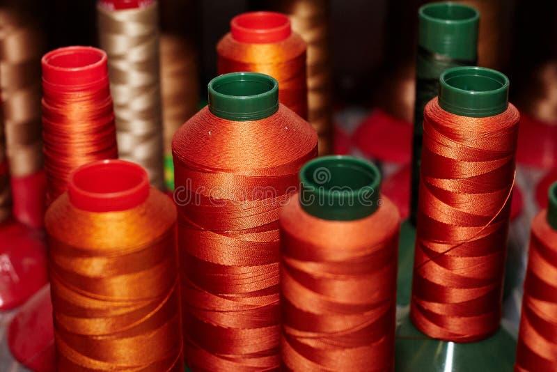 不同,五颜六色的缝合针线,皮革零件的,安排在架子,用于鞋子的生产,提包 免版税库存照片