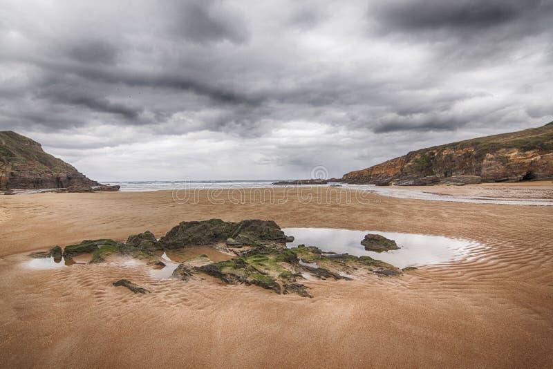 不尽的海滩在阴暗天空下 图库摄影