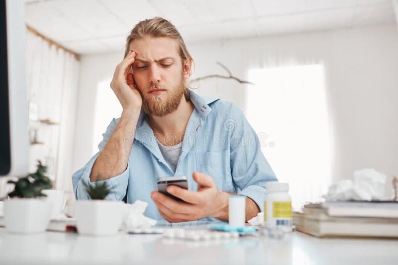 不快乐地看智能手机屏幕的有胡子的金发男性办公室工作者,倾斜在他的手肘,坐在桌上 库存照片