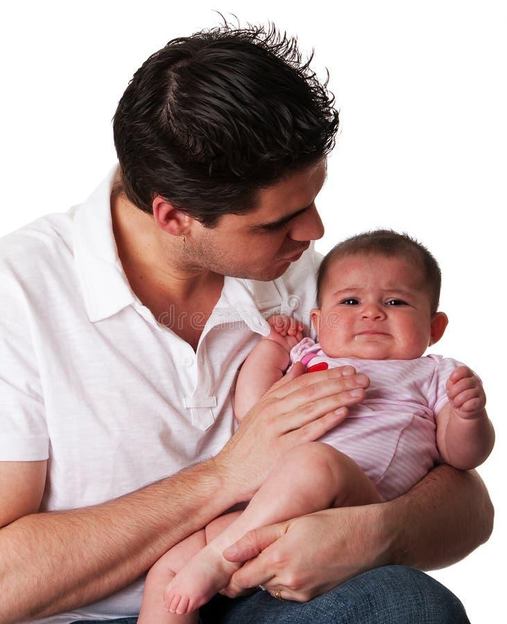 不快乐婴孩镇定的女儿的父亲 免版税库存照片