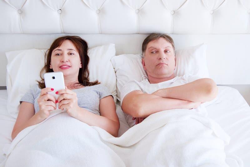 不快乐的中部变老了人神色在她的有一个手机的妻子在卧室,现代人问题 免版税库存图片