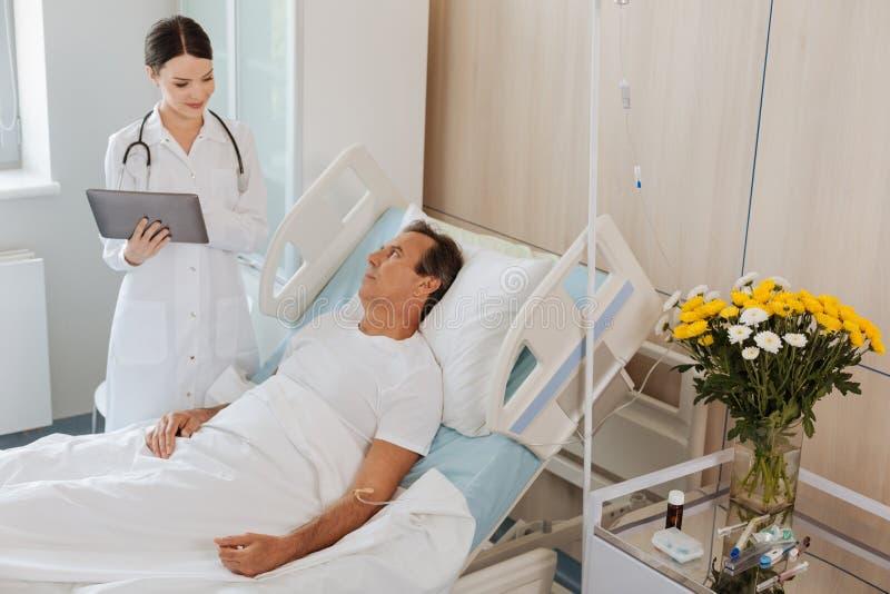 不快乐的中部变老了停留在医院的人 免版税图库摄影