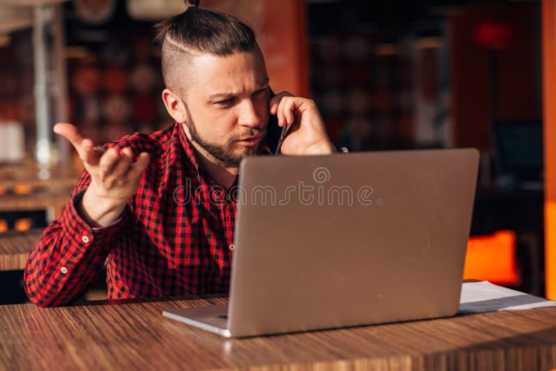 不快乐的商人谈话在咖啡馆的电话 库存图片