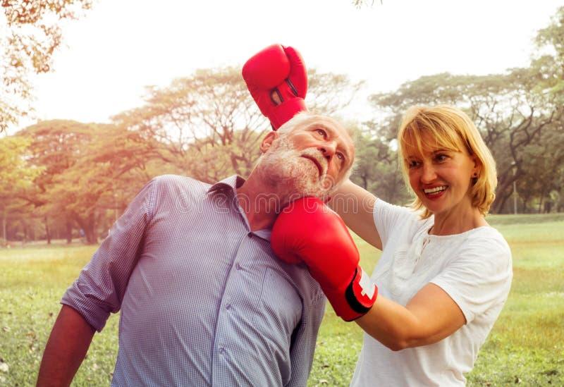 不快乐的夫妇喜爱战斗在公园背景的拳击红色手套 在关系,终止的问题 库存照片