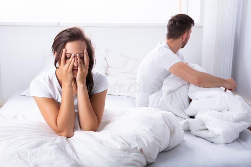 不快乐的夫妇坐床 库存照片