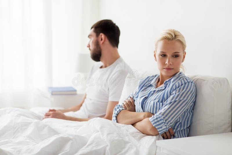 不快乐的夫妇有冲突在床在家 免版税库存照片