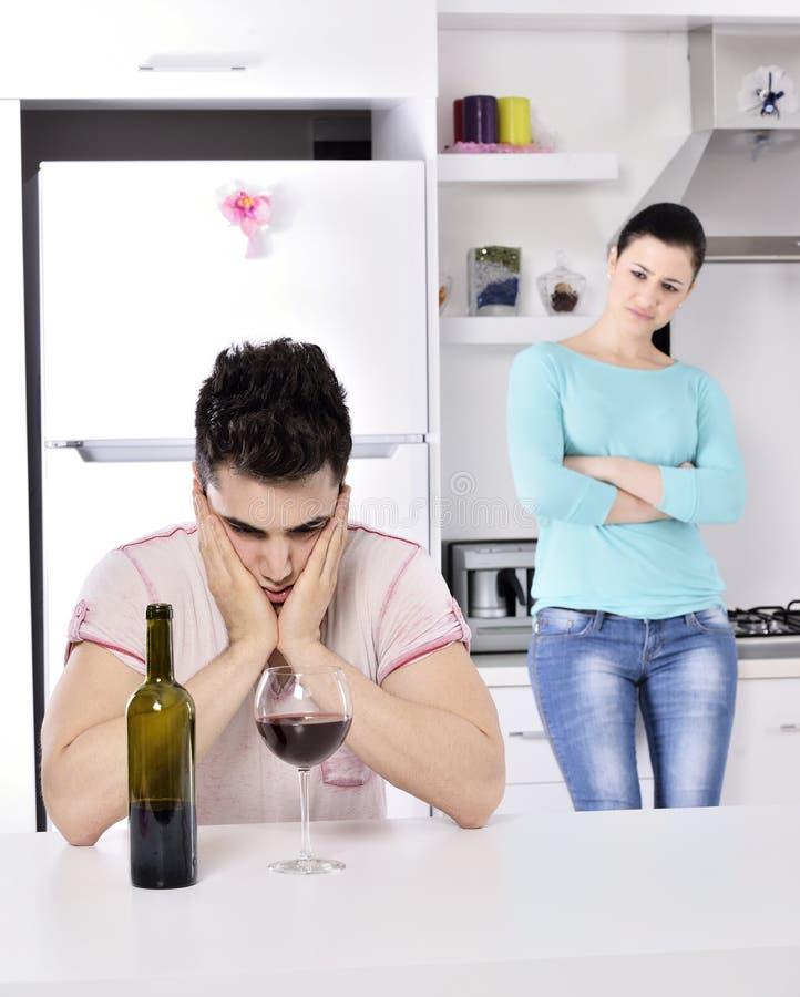 不快乐的夫妇红色藤在厨房里 免版税库存照片