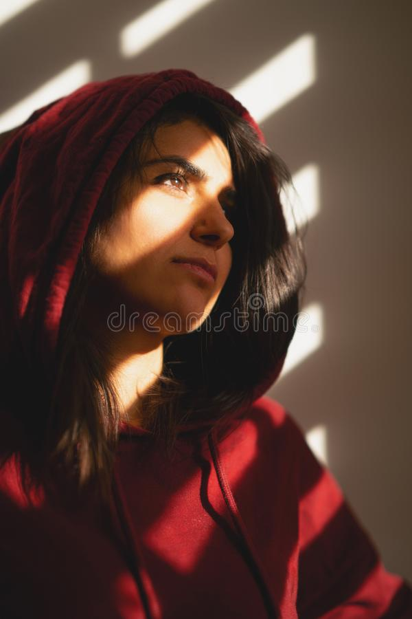 不快乐的女孩站立单独在窗帘 图库摄影