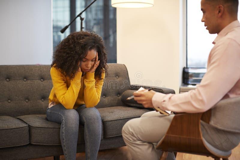 不快乐的妇女坐与男性顾问的长沙发会谈在办公室 免版税库存图片