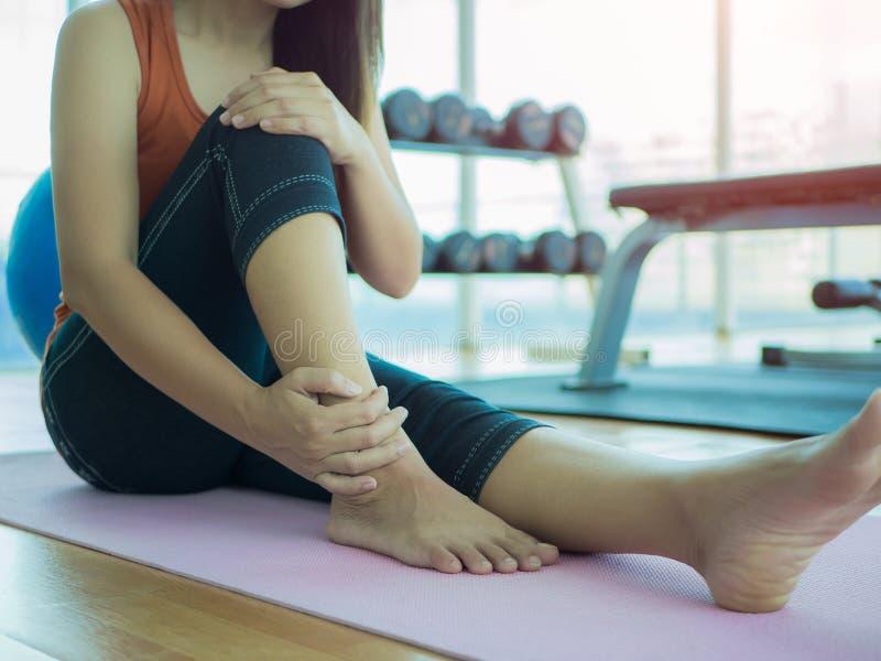 不快乐的妇女坐瑜伽席子以脚踝受伤 免版税库存照片