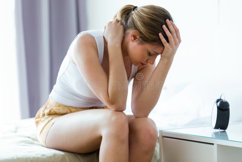 不快乐的孤独的沮丧的少妇在家坐床 消沉概念 免版税库存图片