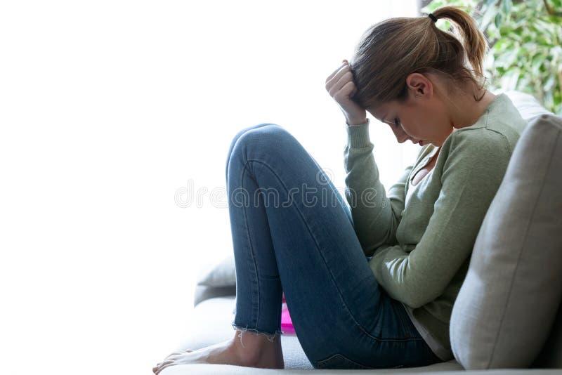 不快乐的孤独的沮丧的少妇在家坐沙发 消沉概念 免版税库存图片
