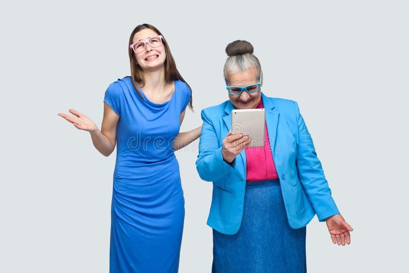 不快乐的少妇常设幸福老妇人神色在桌里 免版税图库摄影