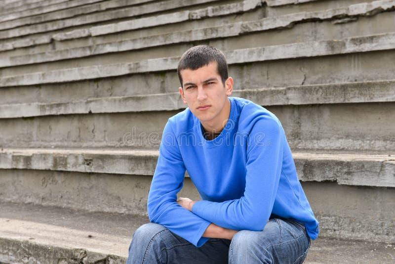 不快乐的少年学生外面坐体育场跨步 库存照片