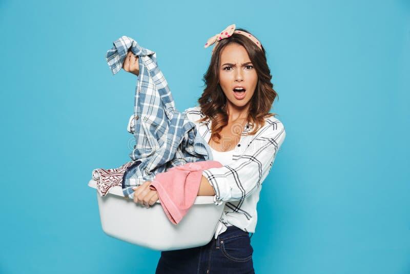 不快乐的年轻主妇20s运载的洗衣篮机智照片  库存照片