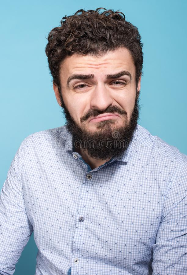 不快乐的年轻人演播室画象有一副鬼脸的在他的面孔 图库摄影