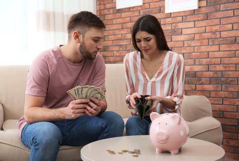 不快乐的年轻加上金钱在家 免版税图库摄影
