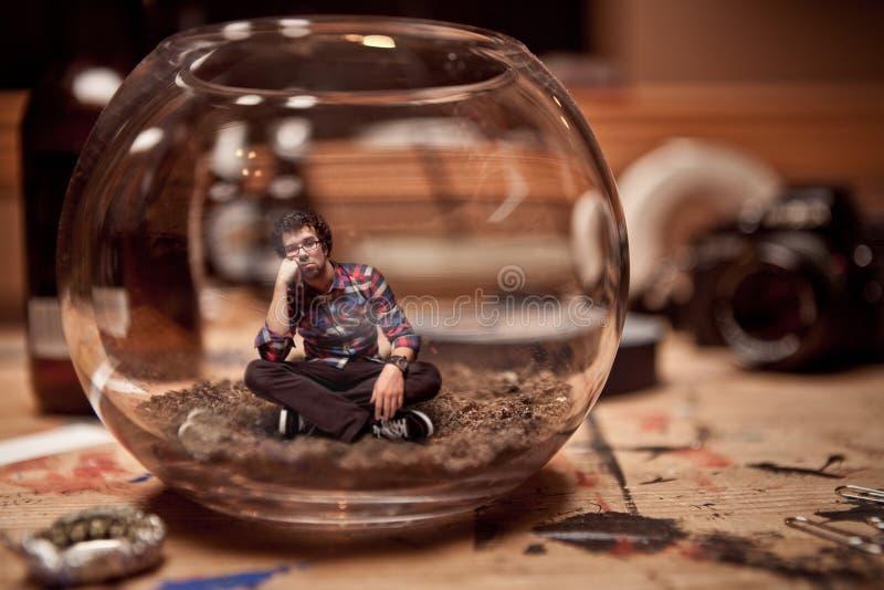 不快乐的微型人被困住在fishbowl里面。 免版税库存照片
