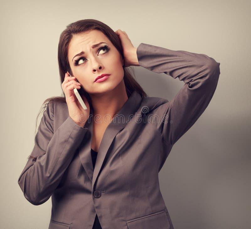 不快乐的担心的女商人谈话在手机和looki 库存图片